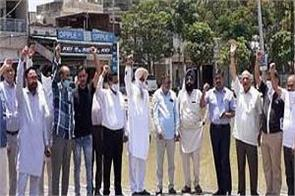 arhats chanting slogans on poor drainage and sanitation in grain market