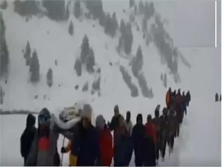 policemen villagers walking in snow carrying sick policeman lahaul spit